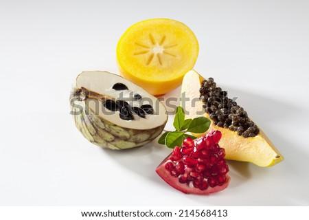 Exotic fruits, papaya, pomegranate, cherimoya, kaki slices on white background - stock photo