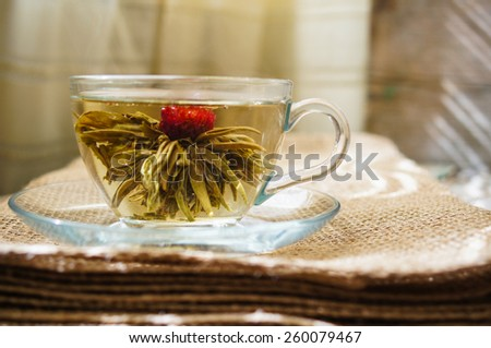 Exotic green tea with flowers in glass teapot on bright background - stock photo