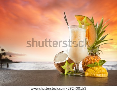 Exotic summer drink served on stone. Blur beach as background - stock photo