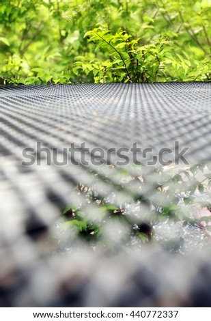 Expanded metal floor in garden.Very shallow depth of field composition. - stock photo