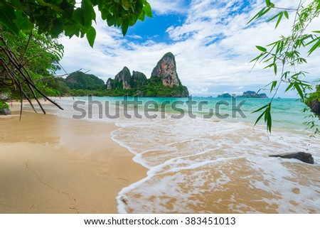Expansive view of the awesome greenish turquoise waving Andaman Sea and the scenic golden beach of Railey Bay, Krabi, Southern Thailand, during summer and monsoon season. - stock photo