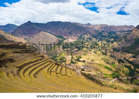 Expansive view of the glowing majestic concentric terraces of Pisac, Inca's site in Sacred Valley, major travel destination in Cusco region, Peru. Dramatic sky. - stock photo