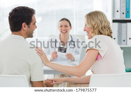 Expectant couple talking while counsulting doctor in clinic - stock photo