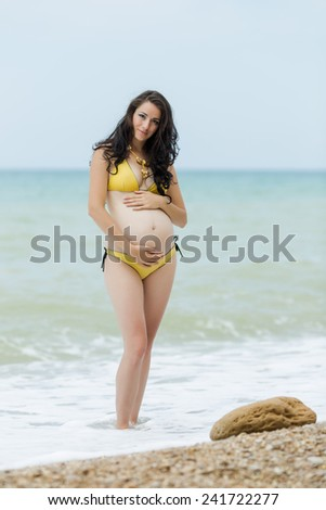Expectant mother embracing own tummy looking at camera. Pregnant woman in yellow bikini posing on the beach - stock photo