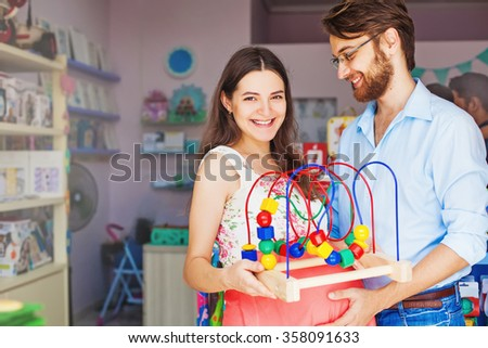 Expectant parents buying baby toy - stock photo