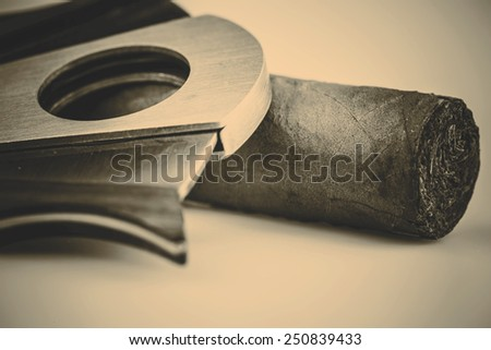 Expensive cigar and cutter on a white background - retro style - stock photo