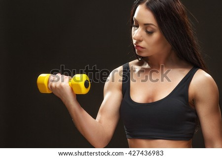 Experienced and concentrated. Studio shot of a calm sporty woman lifting dumbbells on black background. - stock photo