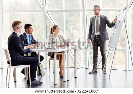 Experienced businessman by whiteboard explaining data to colleagues at seminar - stock photo