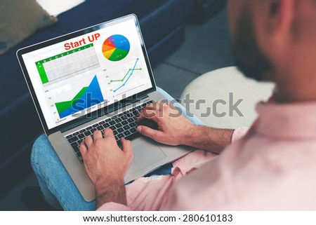 Experienced businessman looking at financial data with graphics and charts while work on a laptop computer, young entrepreneur typing text on notebook keyboard, male freelancer analyzing performance - stock photo