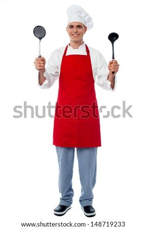 Experienced chef displaying kitchen utensils - stock photo