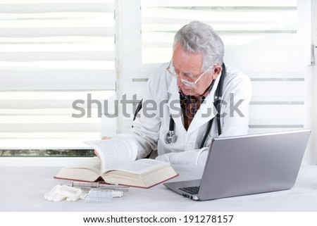 Experienced doctor researching in books and on internet in his office  - stock photo