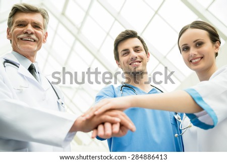 Experienced doctor with medical interns putting hands together. - stock photo