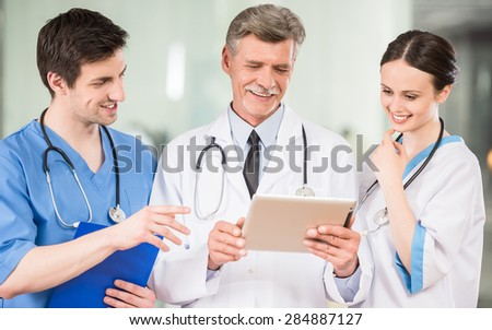 Experienced male doctor looking at digital tablet at doctor's office. - stock photo