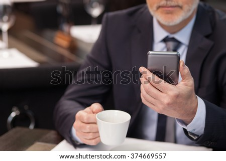Experienced mature businessman is waiting for his business partner in cafe. He is drinking coffee and using a mobile phone. The man is sitting at the table with confidence - stock photo