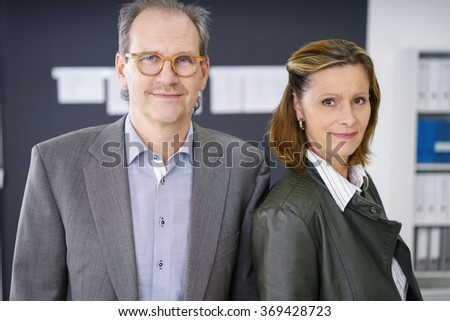 experienced middle-aged business team standing in the office looking at the camera - stock photo