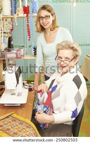 Experienced seamstress and her assistant are showing them work on sewing machine at workshop  - stock photo
