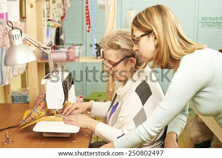 Experienced seamstress is teaching her assistant to work on sewing machine at workshop - stock photo