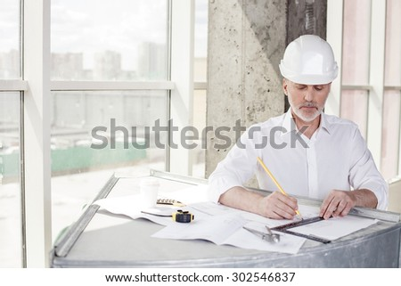 Experienced senior architect is working on plan of building with a ruler and pencil. He is standing near a surface, on which a blueprint is situated. The men is looking at it with concentration - stock photo