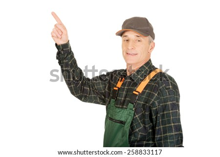 Experienced smiling gardener in uniform pointing up - stock photo