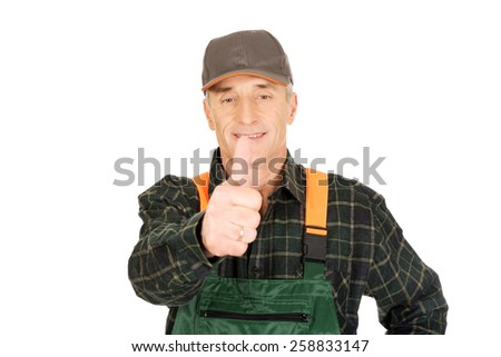 Experienced smiling gardener in uniform with thumbs up - stock photo