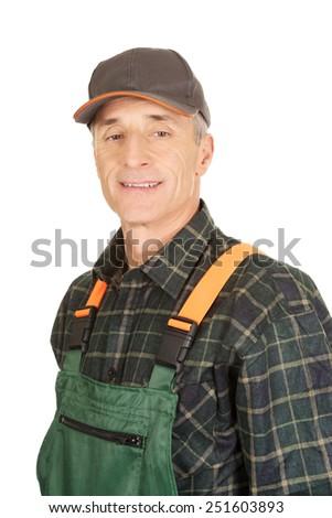 Experienced smiling gardener standing in uniform - stock photo