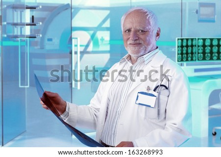 Experienced white-haired male doctor checking MRI scan at hospital - stock photo