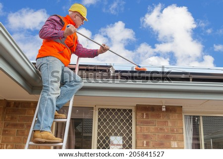experienced worker cleaning solar panels on house roof - stock photo