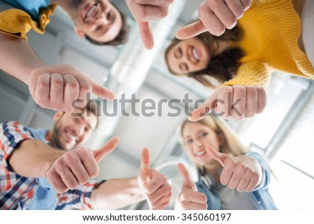 Experienced young colleagues are showing ok sign. They are standing and looking down with joy. The men and women are laughing - stock photo