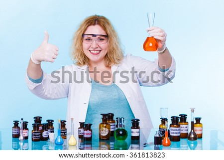 Experiments in laboratory. Happy chemist woman or student girl scientific researcher with chemical glassware test flask making ok hand sign on blue - stock photo