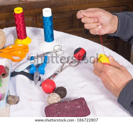 Expert hands crafting  leather balls for traditional pelota sport - stock photo