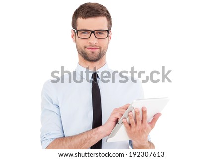 Expert in digital technologies. Cheerful young man in formal wear working on digital tablet and smiling while standing isolated on white background - stock photo