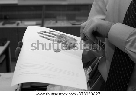 Expert looks at the paper with the imprint of his hands. investi - stock photo