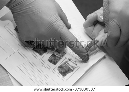 Expert takes a fingerprint of the suspect - stock photo