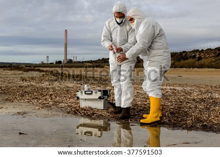 Experts analyze the water in a contaminated environment. / Analysis Water in the River - stock photo