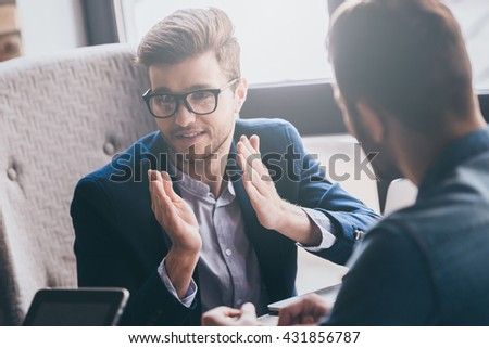 Explaining his point of view. Young handsome man in eyeglasses gesturing and looking away while sitting at the desk with his colleagues - stock photo