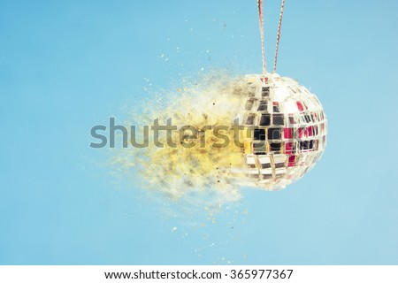 Exploding disco mirror ball on blue background. Concept of wild nightlife, extreme clubbing and hot crazy party. - stock photo