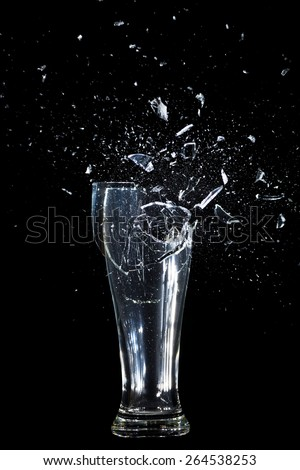 Exploding Glass cup shattering over black background. - stock photo