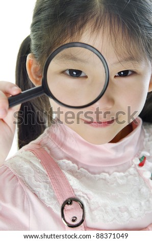 Exploration. A little girl peers at the camera through a magnifying glass. - stock photo