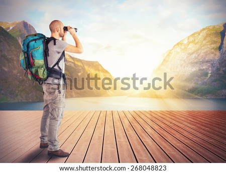 Explorer observes a lake in the mountains - stock photo