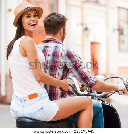 Exploring new places together. Rear view of beautiful young couple riding scooter together while beautiful woman looking over shoulder and smiling - stock photo