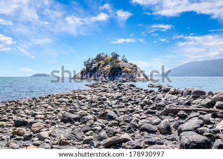 Exposed rocks due to low tide provides a natural rock trail to Whytecliff Island on Whytecliffe Park beach in West Vancouver, British Columbia - stock photo