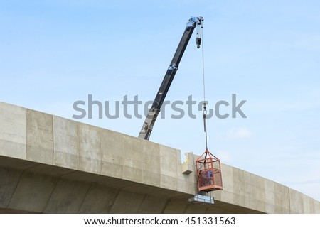 Express way,the express way under construction with the crane.The worker in the crane basket at the express way construction site with the blue sky. - stock photo