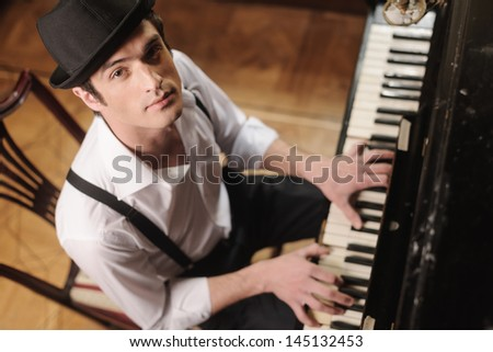 Expressing myself with music. Top view of handsome young men playing piano and looking at camera - stock photo