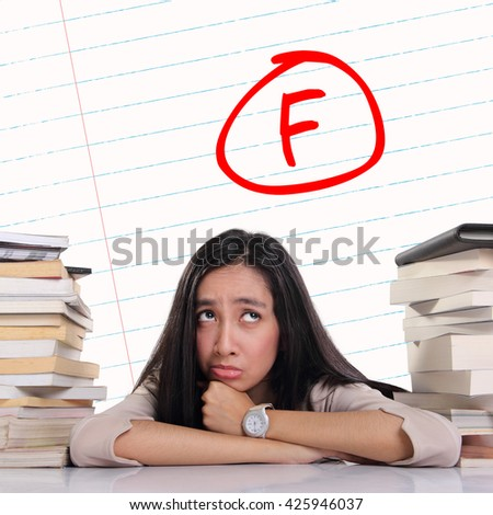 Expression of an Asian school girl on her desk feeling upset, looking at handwritten F score on a paper background - symbol of failure - education concept - stock photo