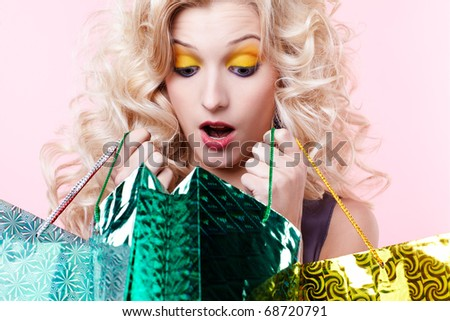 expression portrait of customer blonde girl with shopping bags looking shocked - stock photo
