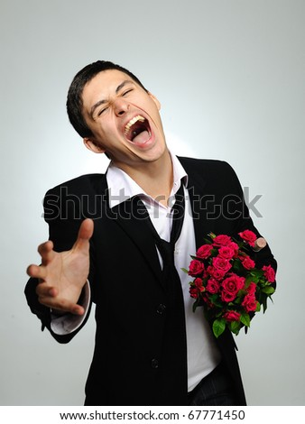 Expressions. screaming husband holding rose flower and vine bottle prepared for a date. gray background - stock photo