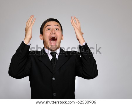 Expressions - Young handsome business man screaming of joy and luck. studio shot - stock photo