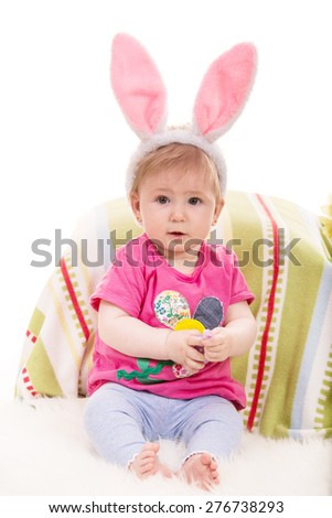Expressive baby girl with fluffy bunny ears holding Easter egg - stock photo
