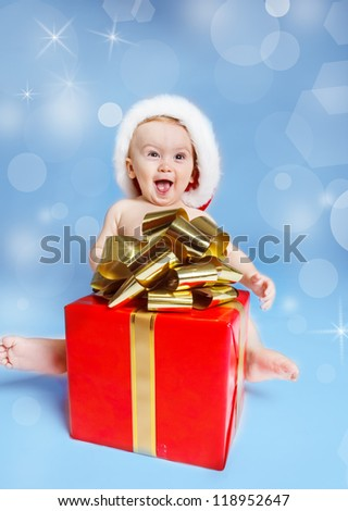 Expressive baby sitting with Christmas present - stock photo
