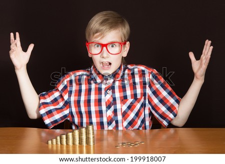 Expressive boy with the piles of coins in front of him looking at the camera - stock photo